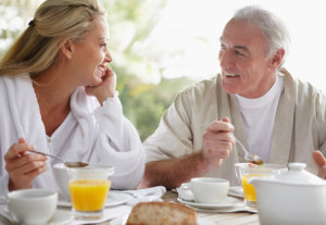 Lovely mature couple having a chat while at breakfast table